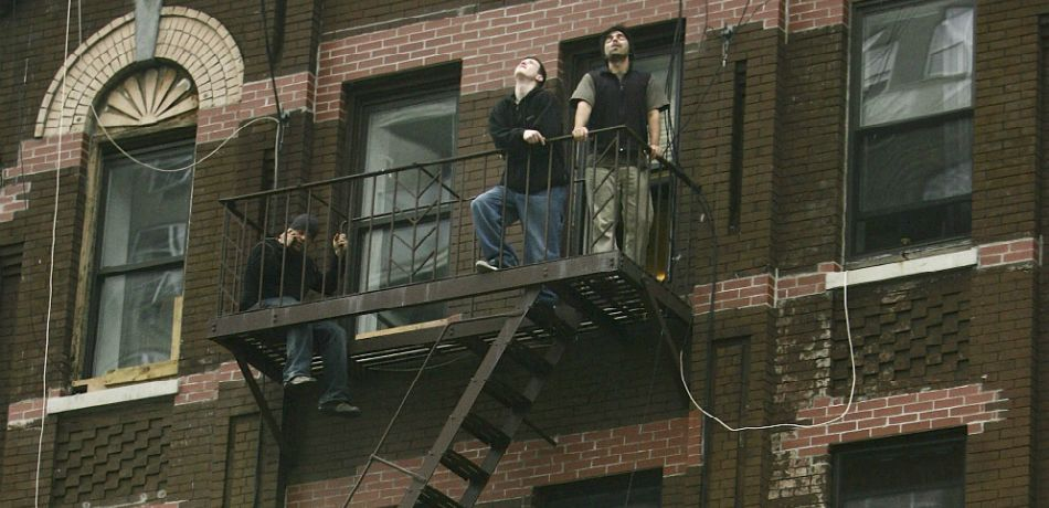 Residents stand on a fire escape near the site of a plane crash into the Belaire Condo high rise building at 524 E. 72nd St.