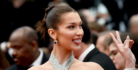 Bella Hadid sticks her tongue out and flashes the peace sign playfully at a red carpet event.