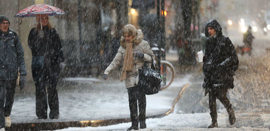 New York City residents walk the streets during the first snowfall.