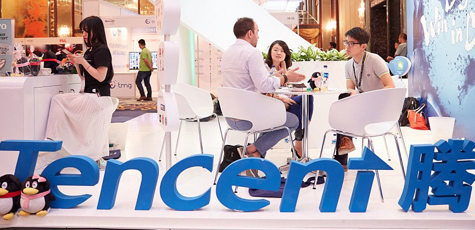 Visitors and exhibitors network at the Tencent booth during the 2016 Sportel Asia Conference in Singapore.