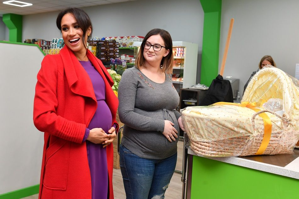 Meghan Markle presents Angela Midgley with a Moses basket at 'Number Seven', a 'Feeding Birkenhead' citizen's supermarket and community cafe, on January 14.