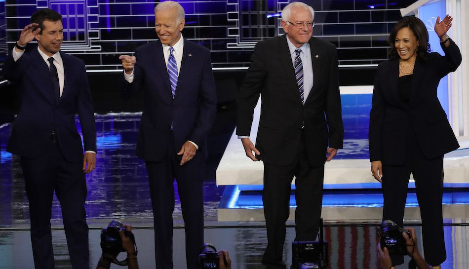 Democratic presidential candidates stand on the debate stage.