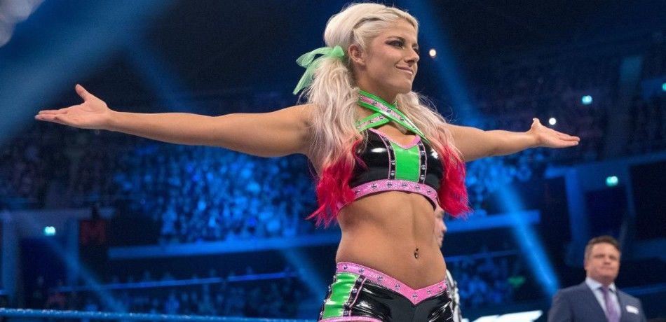 Alexa Bliss poses on the apron before her match