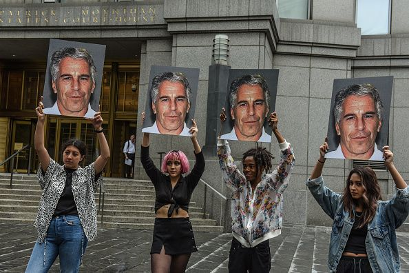 """NEW YORK, NY - JULY 08: A protest group called """"Hot Mess"""" hold up signs of Jeffrey Epstein in front of the Federal courthouse on July 8, 2019 in New York City. According to reports, Epstein will be charged with one count of sex trafficking of minors and one count of conspiracy to engage in sex trafficking of minors. (Photo by Stephanie Keith/Getty Images)"""