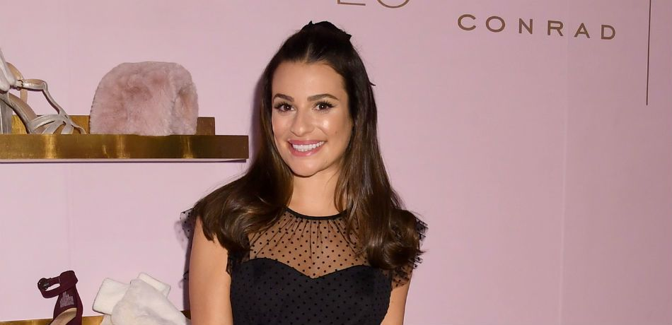 Lea Michele poses for a photo in a black top.