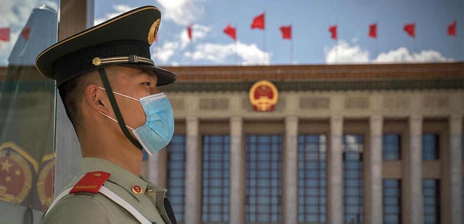 A photo of a Chinese soldier outside a building.