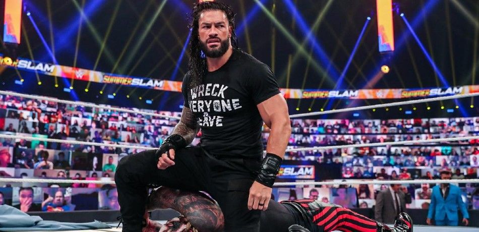 Roman Reigns kneels over a fallen Bray Wyatt
